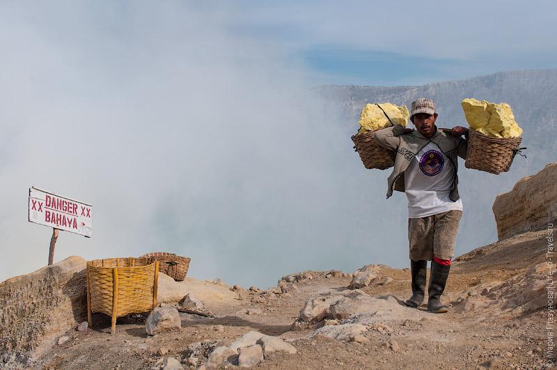 Местный житель несёт серу из вулкана